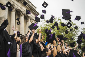 Students on graduation day at Portsmouth university, throwing their mortarboard hats into the air