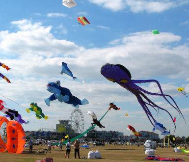 Colourful kites in all different shapes and sizes flying above the beach in Portsmouth, UK.