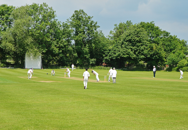 Group of men in white clothes playing cricket in a rural location