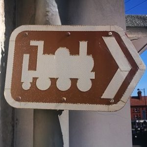 Brown sign with a white train logo