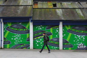 Man walking past old garages where the shutters have been painted to look like there are lots of UFOs