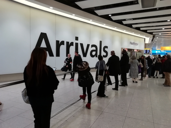 People waiting in the arrivals area of heathrow airport