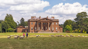 Berrington Hall is a large country house set in grassy parkland with large trees and sheep.