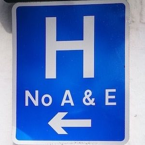 Blue sign with H No A&E and an arrow