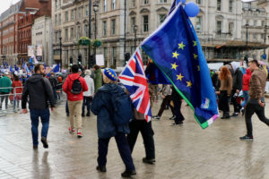 People at a Brexit demonstration. A protester carries a European Union flag and a British flag