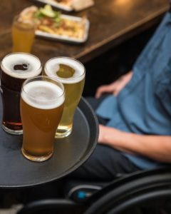 A tray with three types of beer in the foreground. In the background there is a man in a wheelchair