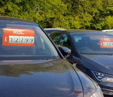 Row of cars for sale with prices shown in the windscreen