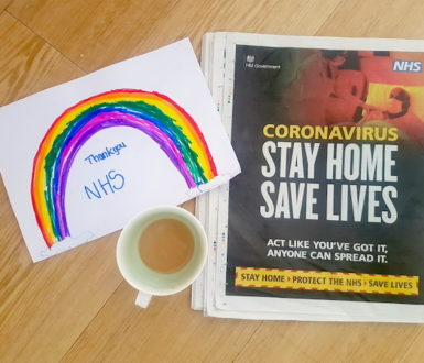 View of a newspaper advert from the government with the words Stay Home, Protect the NHS, Save Lives. Also a cup of tea and a child's drawing of a rainbow