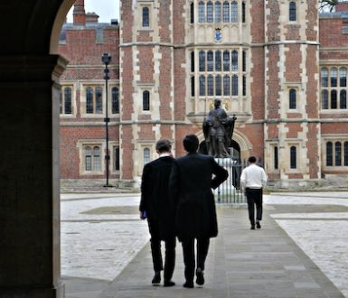 Back view of schoolboys at Eton walking through a very smart courtyward. The boys are wearing long black formal jackets