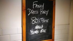 Chalkboard on pub wall with the words 'Fancy dress party 80's theme new years eve'