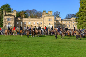 Group of people on horses in front of a large country house. The people are wearing clothes used for foxhunting