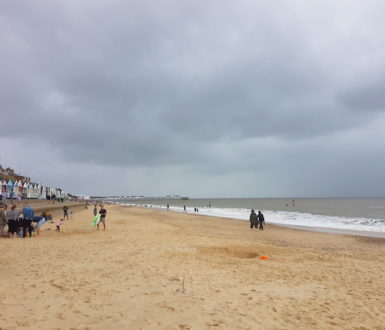 People in coats on a sandy beach with grey skies