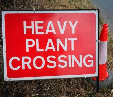 Red sign with the words Heavy Plant Crossing