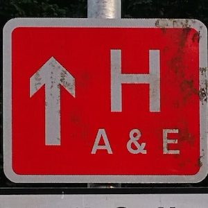 Red sign with H A& E and an arrow