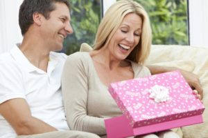 Woman looking fairly excited about a gift she has just opened. A man sits next to her