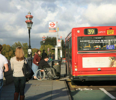 Bus at a bus stop, man in wheelchair is using the ramp access