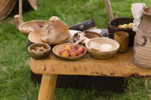 Food from medieval times arranged on wooden plates. Bread, walnuts, plums, apples. Also mead in a ceramic jug.