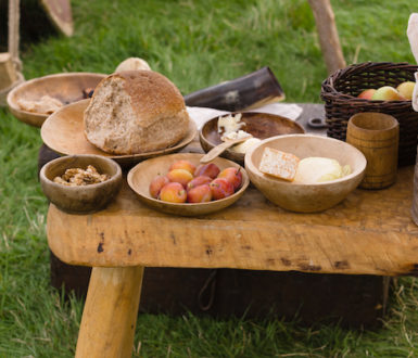 Selection of food from British medieval times including plums, cheese, apples and bread. On wooden plates.