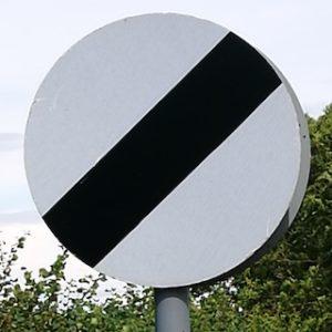 White circular sign with black diagonal stripe