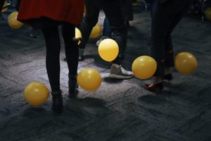 the legs of people dancing, with yellow balloons floating about