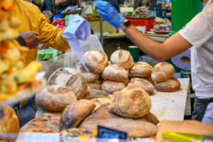 Market stall selling bread. The stallholder is giving change to a person who has just bought something