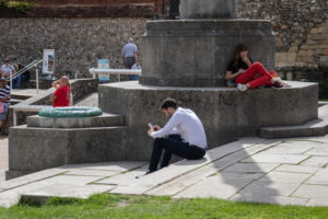 People sitting outside on a sunny day, one man looking at his mobile phone