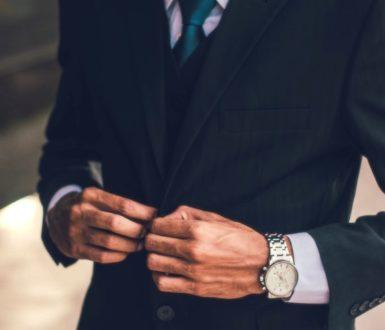 Man buttoning a dark suit