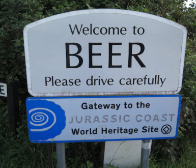A road sign saying Welcome to Beer please drive carefully. Beer is a town in Devon.