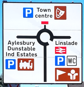 Road sign for a roundabout with a tourist train logo on the left and a British Rail logo on the right