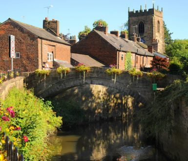 View of a charming village with church in the background and a bridge in the foreground
