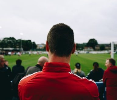 Group of men watching sport, seen from behind
