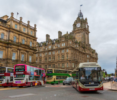 A group of buses of different colours on Princes Street In Edinburgh