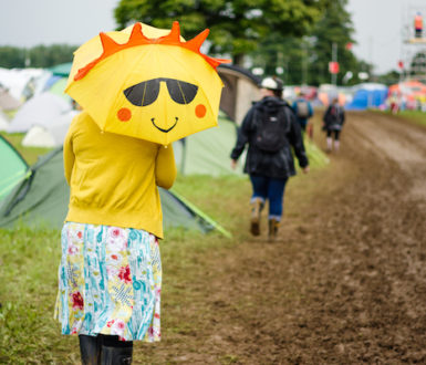 A lady in rubber boots at a muddy festival holding a yellow umbrella that has a smiley sun face