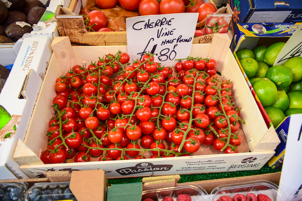 A box of cherry tomatoes on a market stall, priced by the half pound