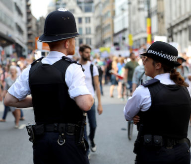 2 police officers viewed from behind in front of a crowd of people