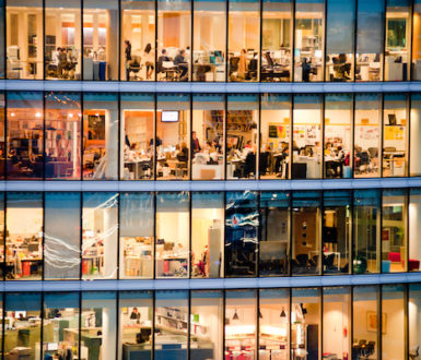 View into glass-walled office at night showing lots of people working