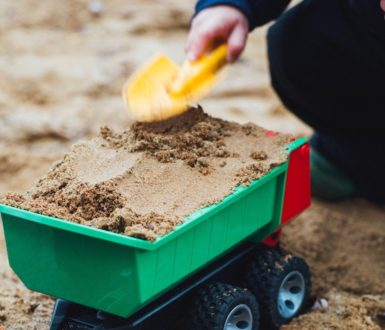 Child putting sand in toy truck