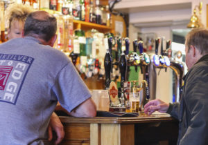 Men sitting at the bar of a pub in front of different beer and ale pump handles
