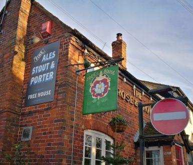 Side of pub building showing a colorful sign hanging from the wall and the words 'free house'