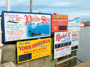 Variety of signs for pleasure boat trips called Pirate and Yorkshireman