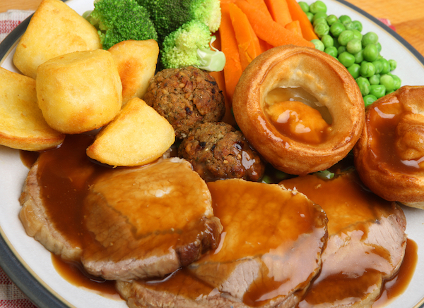 A British roast dinner, consisting of roasted meat, roast potatoes, boiled carrots, peas and broccoli plus a Yorkshire pudding and stuffing balls