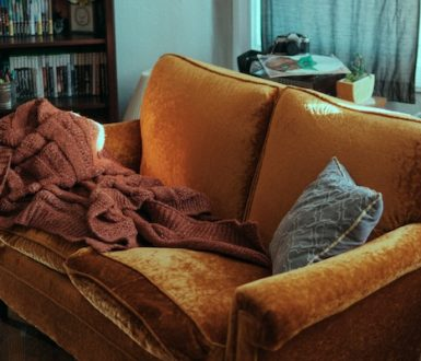 Sofa in a living room. On the sofa is a blanket and cushion