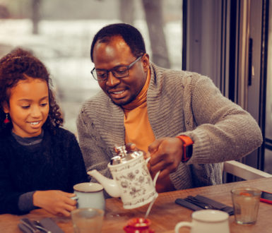 Man pouring tea for his daughter