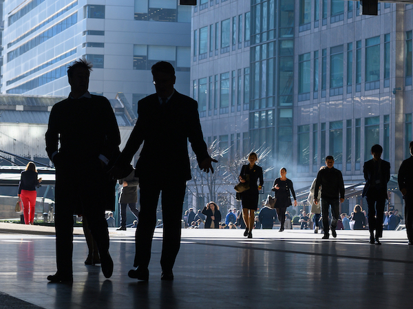 People silhouetted against office buildings