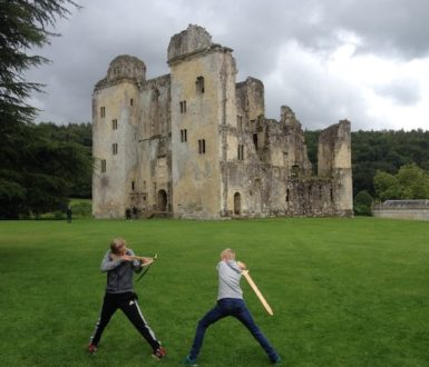 Boys fighting with wooden weapons outside ruined castle