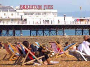 People on deckchairs near Brighton Pier
