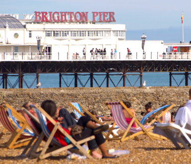 People on deckchairs near Brighton Pier